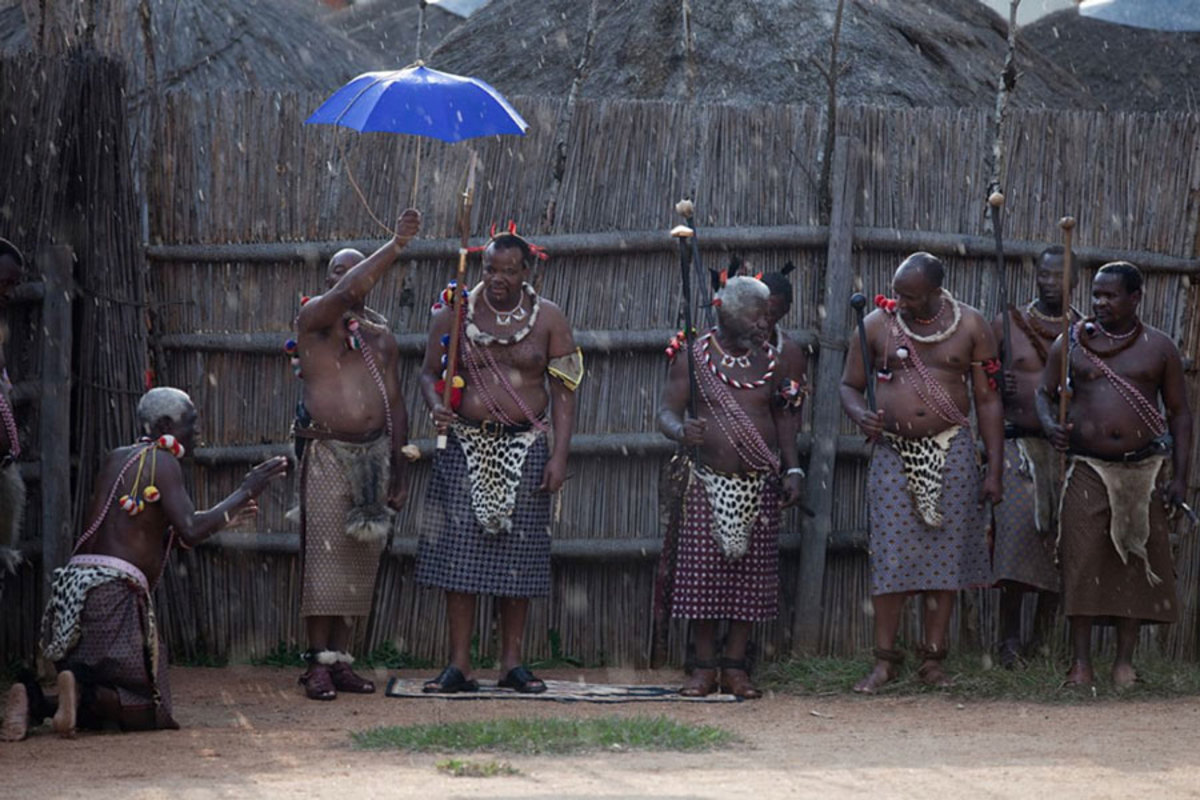King Mswati III and members of the  royal family watch a traditional Reed dance ceremony at the stadium at the Royal Palace