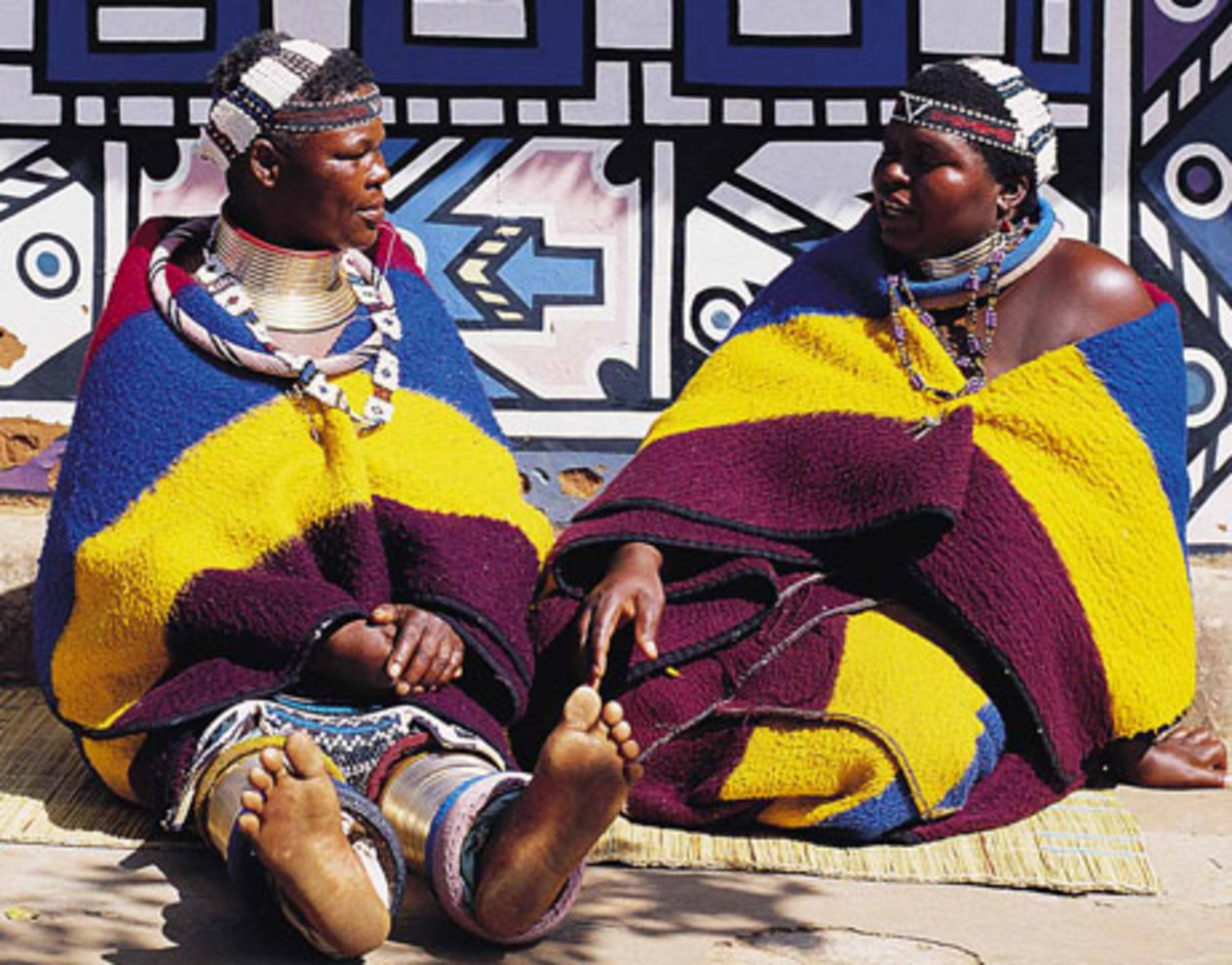 Ndebele Women in full traditional gear and jewelry sitting nex to their art