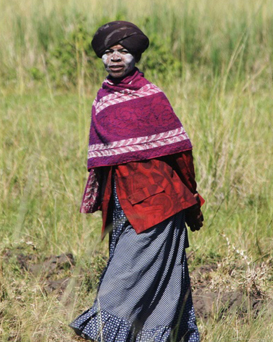 Xhosa woman wearing traditional Xhosa cloth of long skirts, embroidered with horizontal stripes and placed at varying intervals