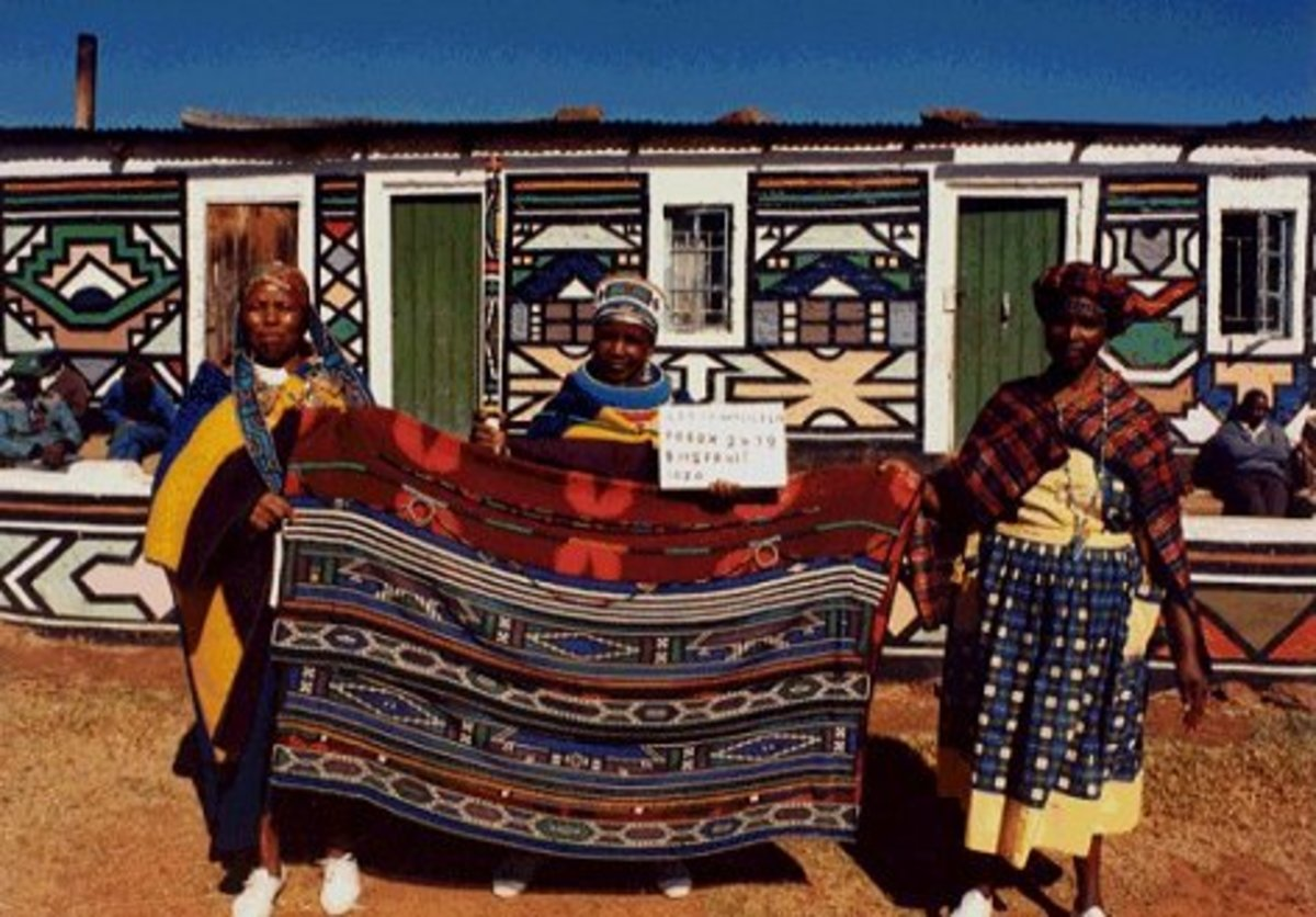 Ndebele Women Sanding Next to their painted houses and holding a traditional Ndebele Blanket