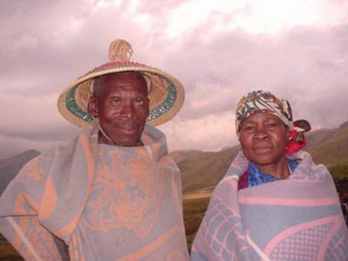 """Basotho People with the Man wearing his 'grass'-made hat called Modianeo"""" and he and his wife waring a """"Kobo""""(Blanket."""