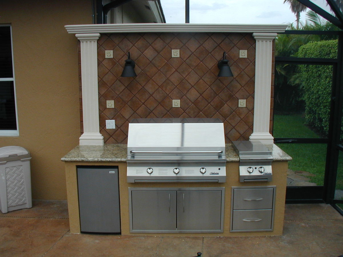 Custom outdoor kitchen with backsplash with lights and a built in Solaire infrared gas grill.