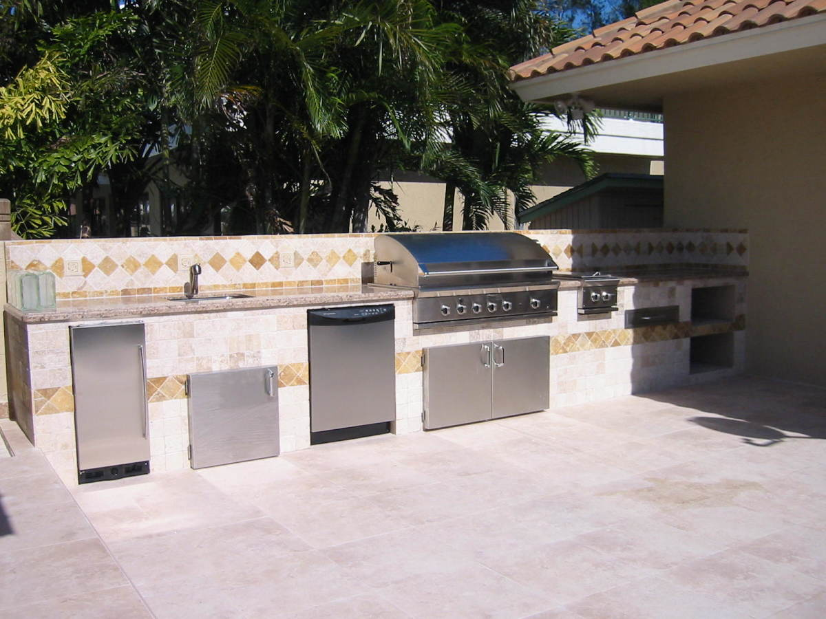Built in DCS gas grill in a custom grill island with refrigeration and a dish washer.