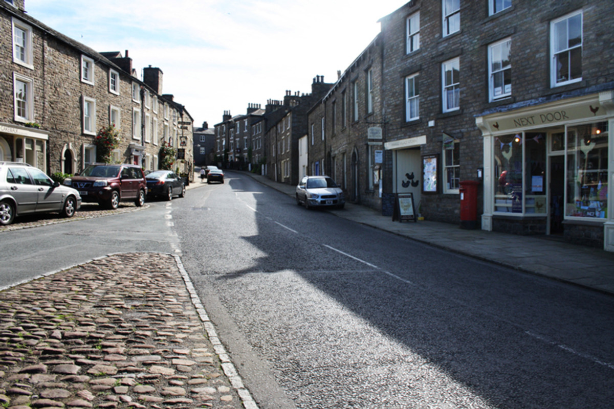 The main street in Askrigg leading down to Bainbridge where the shortest river in England - the Bain - empties under the bridge into the Ure
