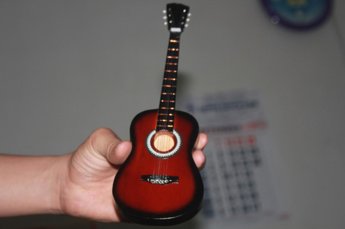 Classic miniature guitar in palm hand