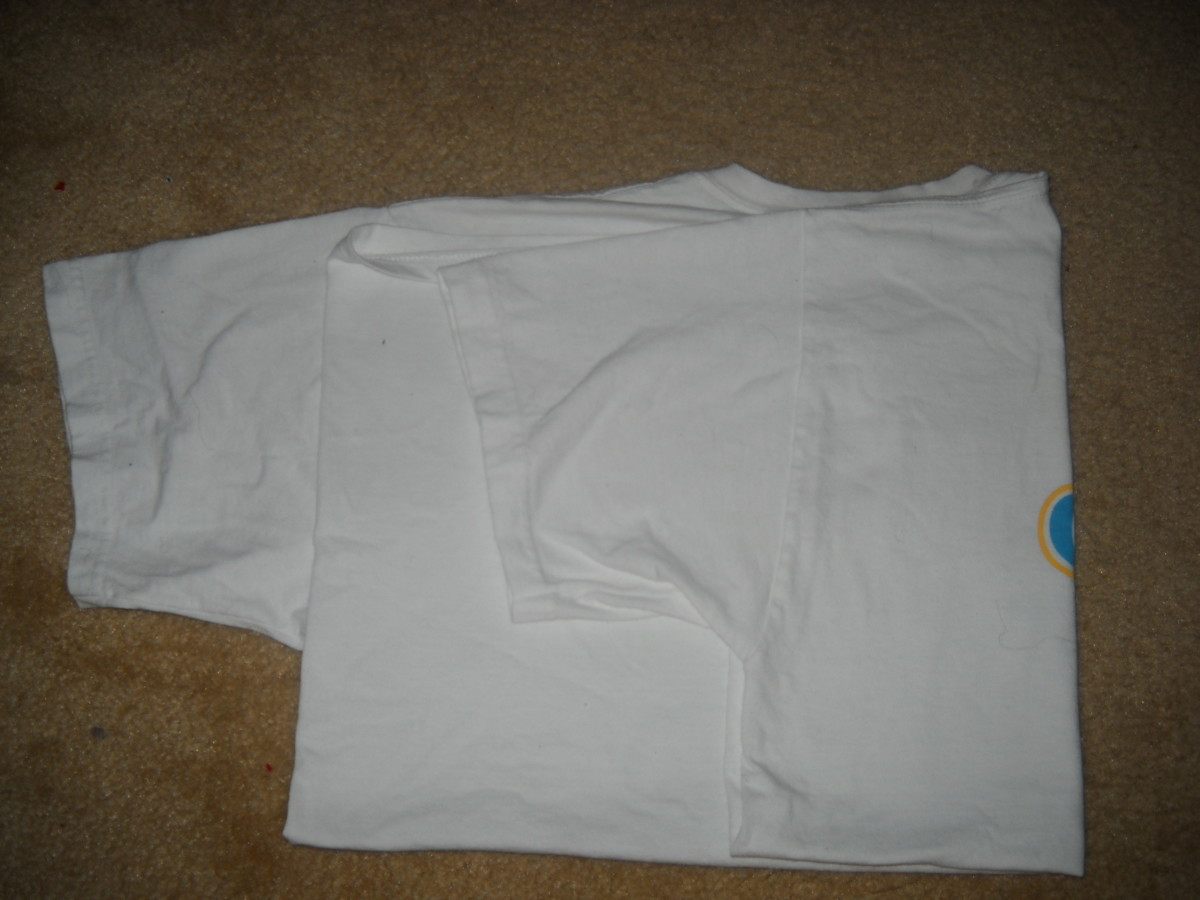 Back view - T shirt arm folded back at the middle of the shoulder.