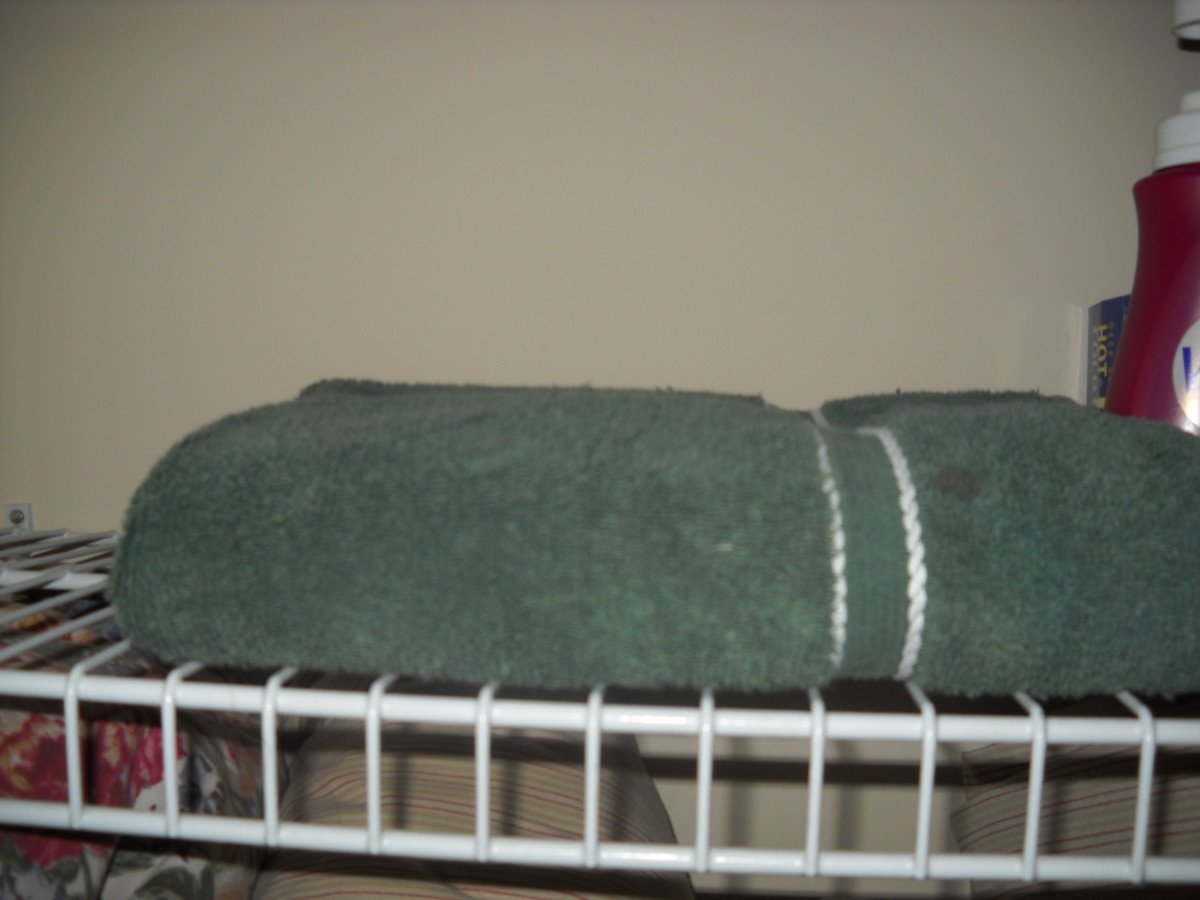 Folded towel on the shelf in the linen closet.