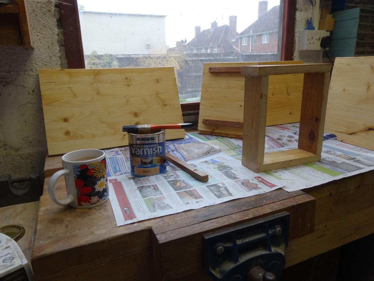Varnishing all the shelving prior to assembling.