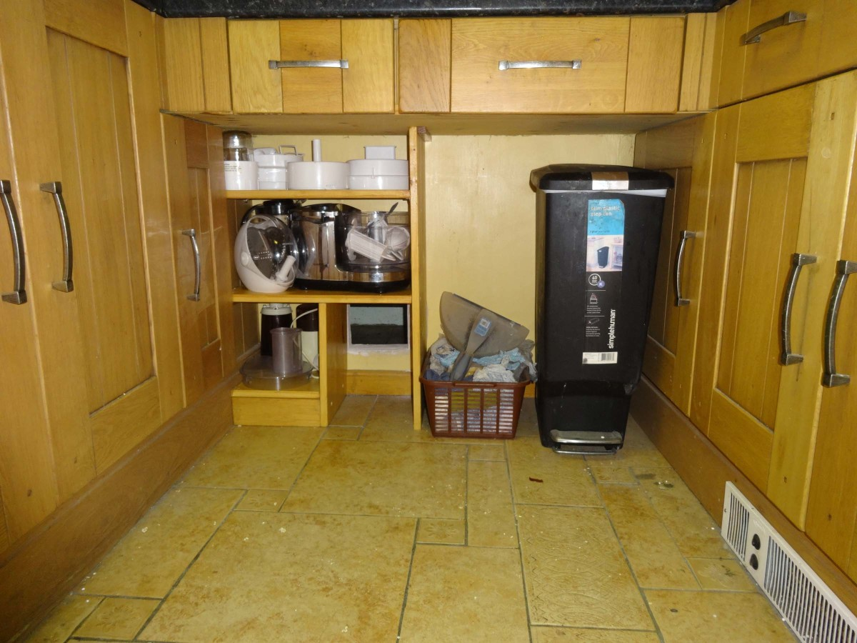 Open shelving fitted into place under the kitchen worktop.
