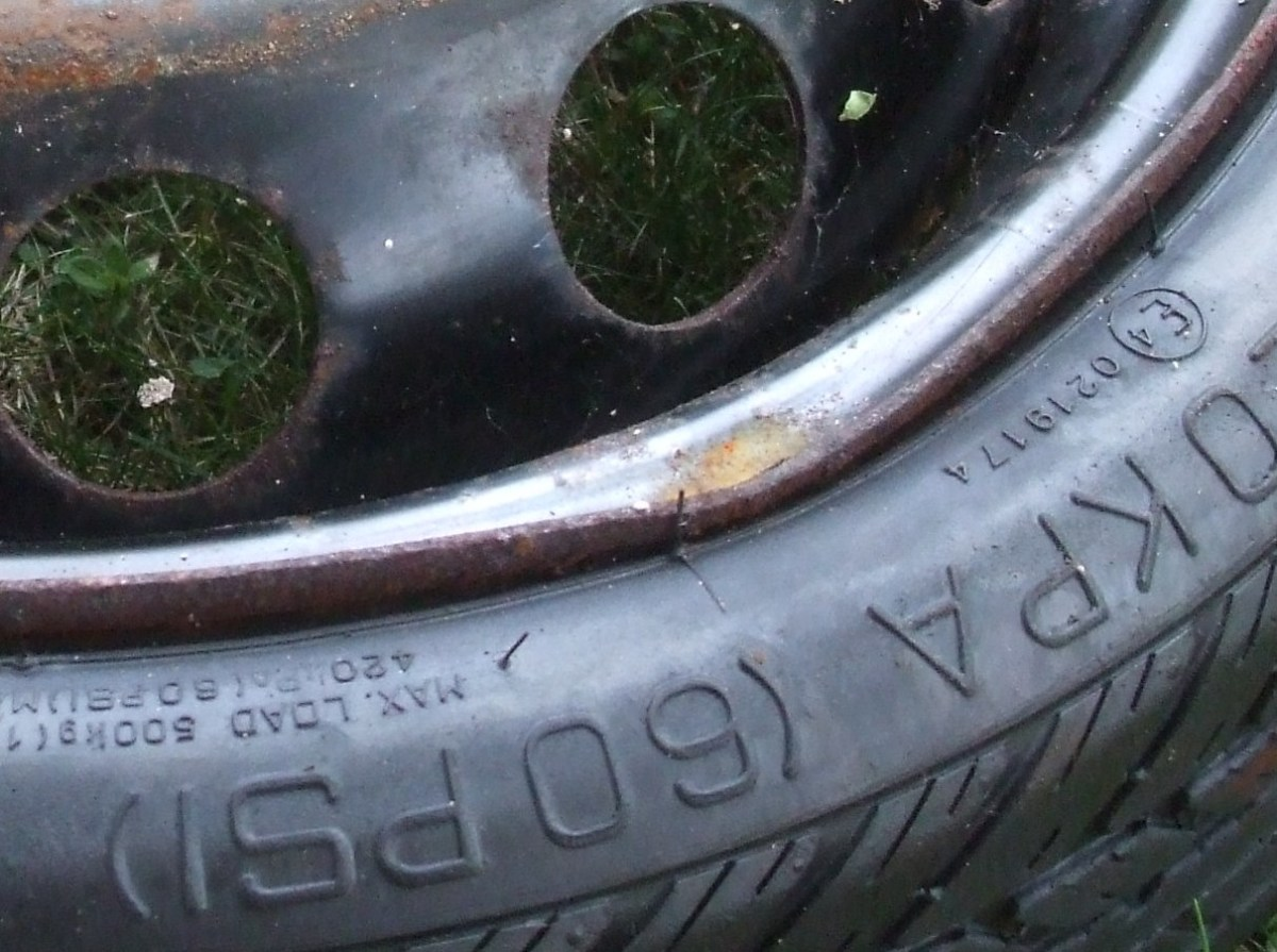 A close-up of a bent rim on a spare tire.