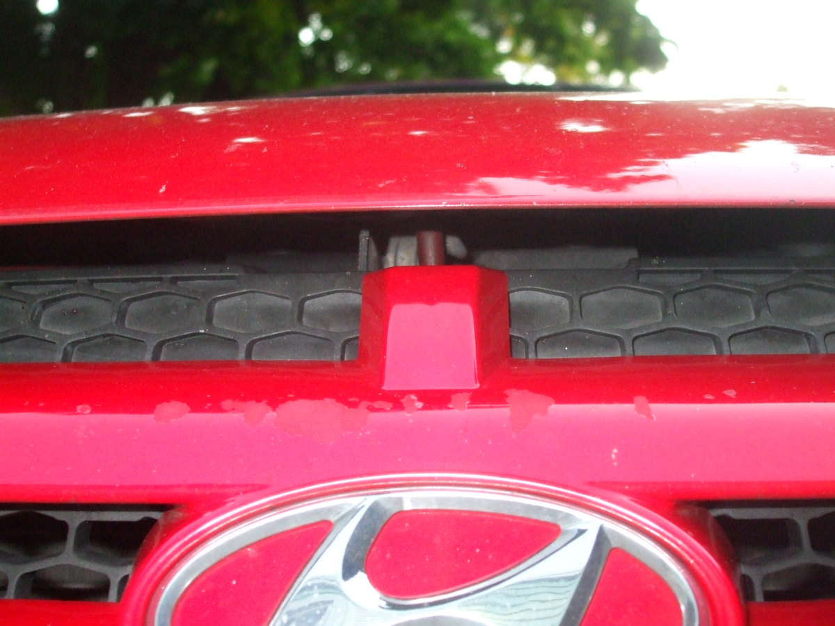 Hood latch on this car is centered behind the red square.