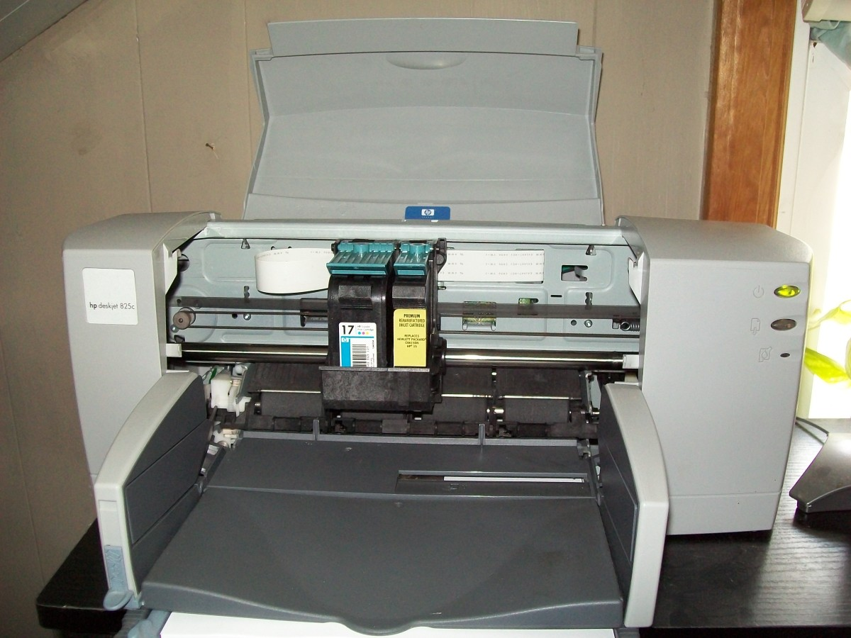 Open cover showing where the ink cartridges go.  An empty color cartridge is still installed while a re-manufactured HP 15 Black ink cartridge is installed.