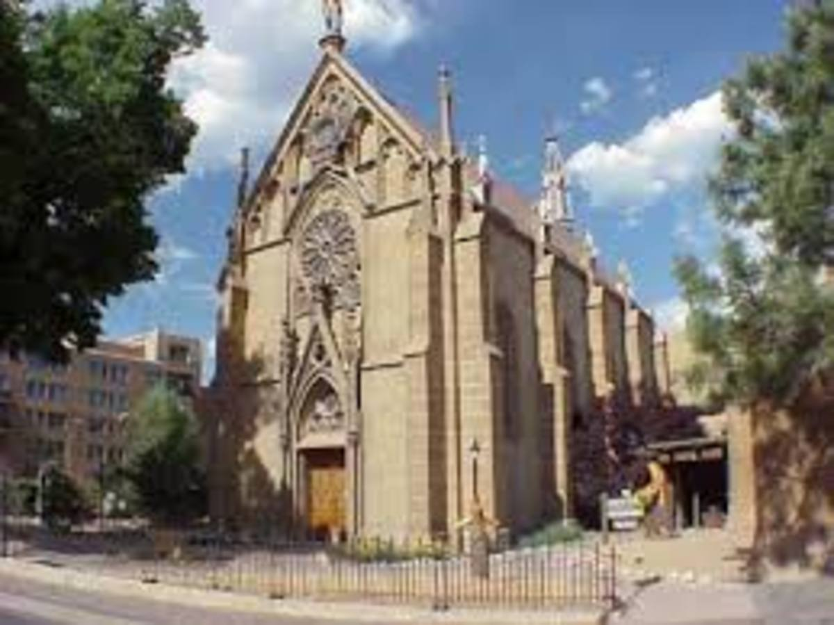 The exterior of the Loretto Chapel in Santa Fe, New Mexico. Entrance to the chapel is along the side in the lower right of the photo. The building in the background on the left is the sprawling and historic La Fonda Hotel