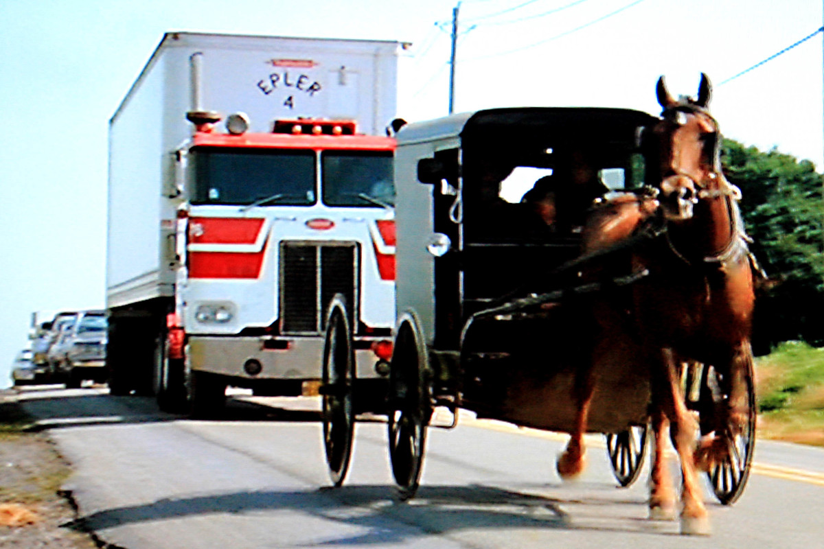 An Amish pony and trap pursued by a massive truck and a long queue of cars