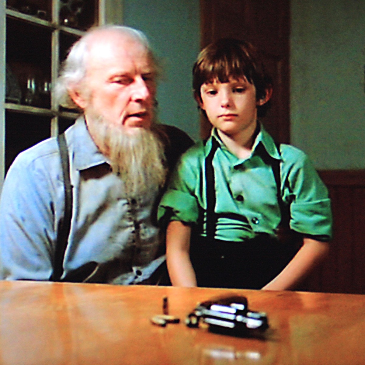Many sequences in the movie highlight the deep conflict between Amish life and John Book's life. Here, Eli Lapp lectures Samuel on the Amish abhorrence of hand guns