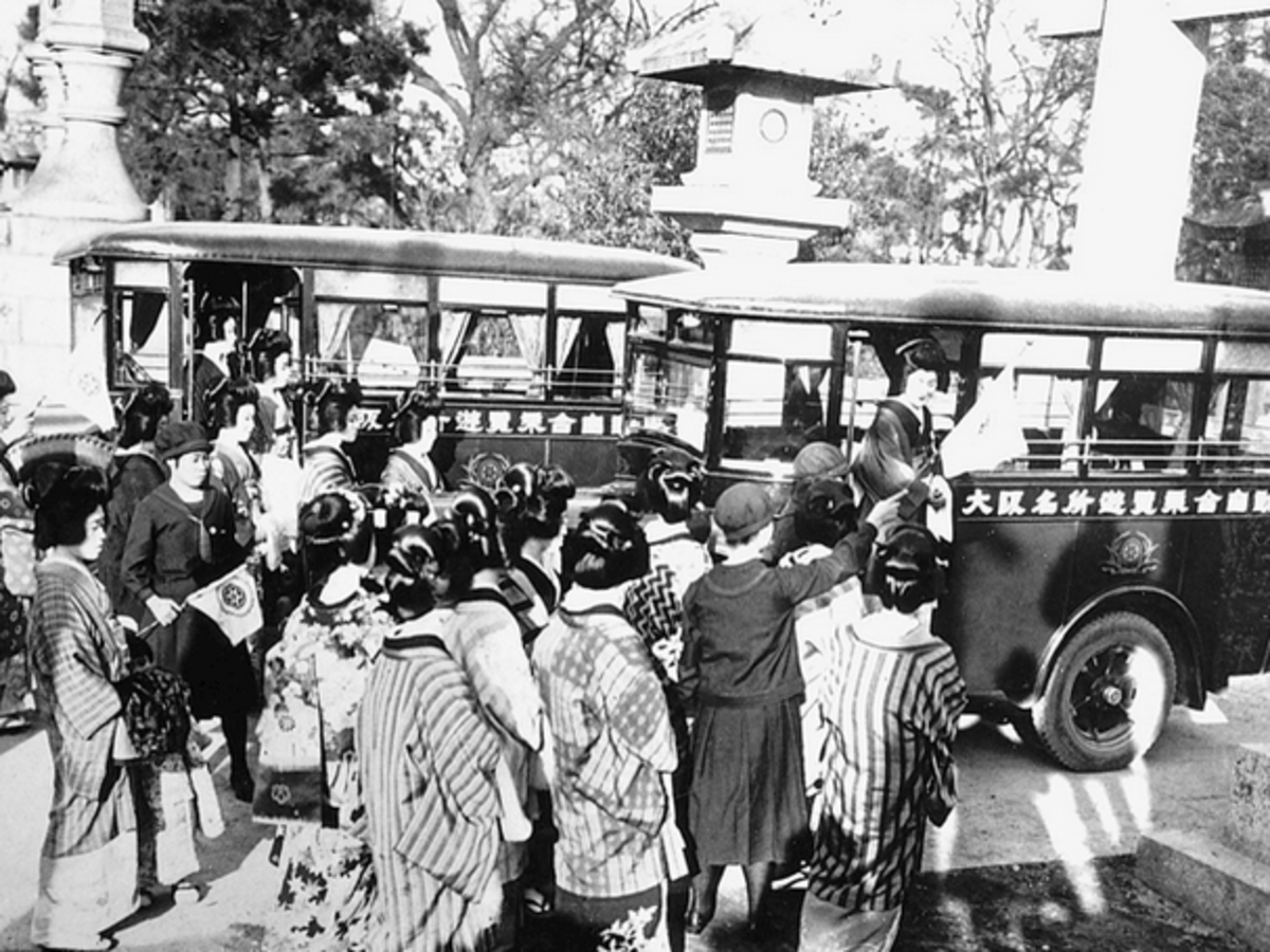 Public transport developed quickly in Japan. This bus in 1929 was already much more sophisticated. Long lines of people are waiting for the bus.