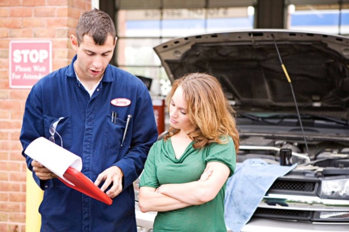 """This shady auto mechanic is thinking: """"Hmm, this gal does not know a thing about cars. So it's time for me to make some big extra money"""""""