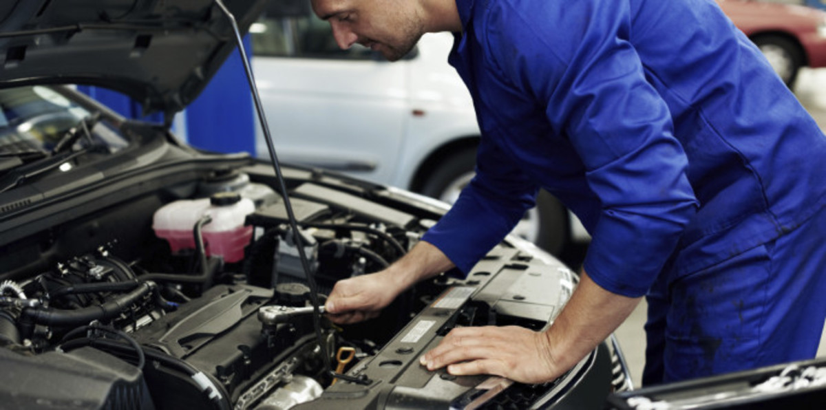 Why is this shady auto mechanic checking under the hood when the problem is a flat tire?