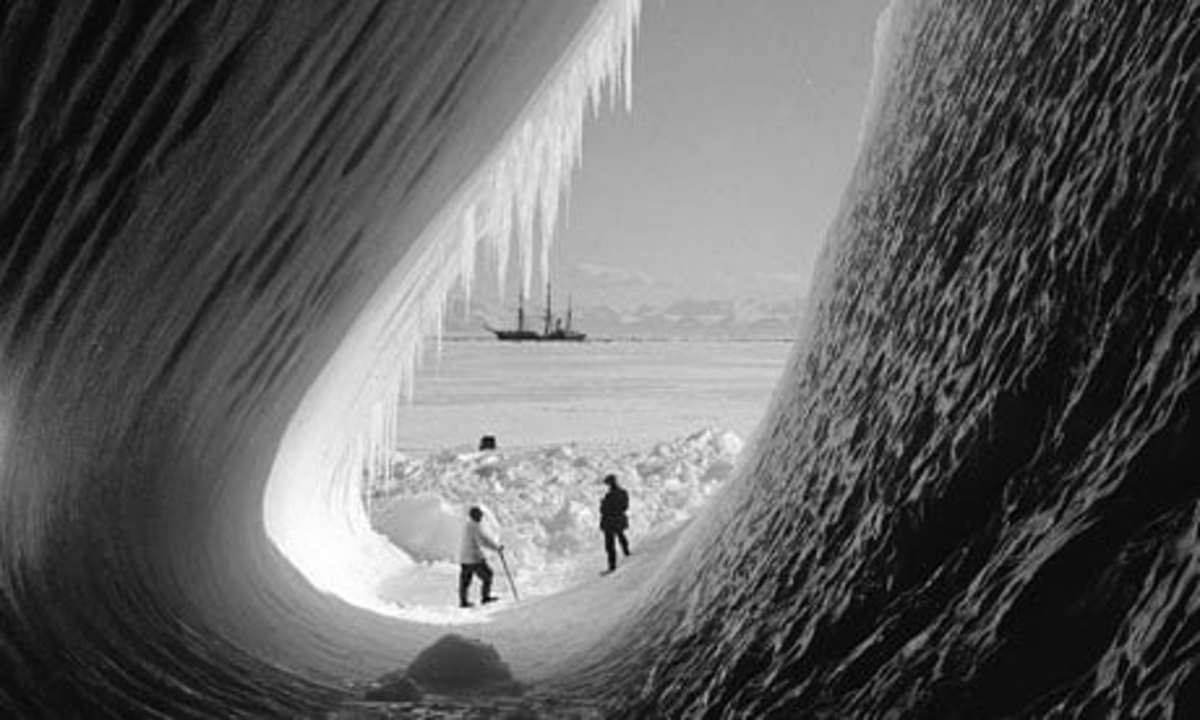 Inside an ice grotto showing the 'Terra Nova' ship in the distance.