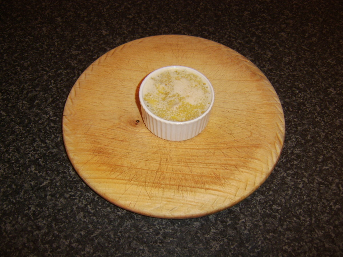 Melted butter is poured in to ramekin with chicken