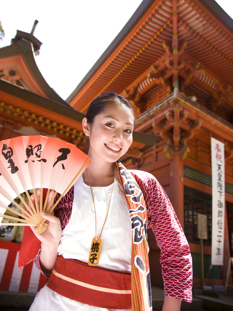 Momoko Tani standing outside of a temple perhaps? She is holding one of those small fans that has the ability to cool you off.