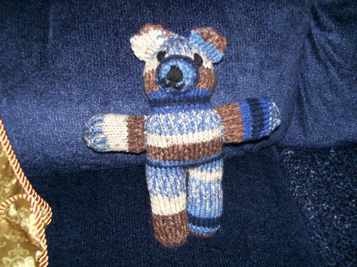 A finished, completed Bear with embroidered eyes, nose and mouth in black 3-ply yarn.