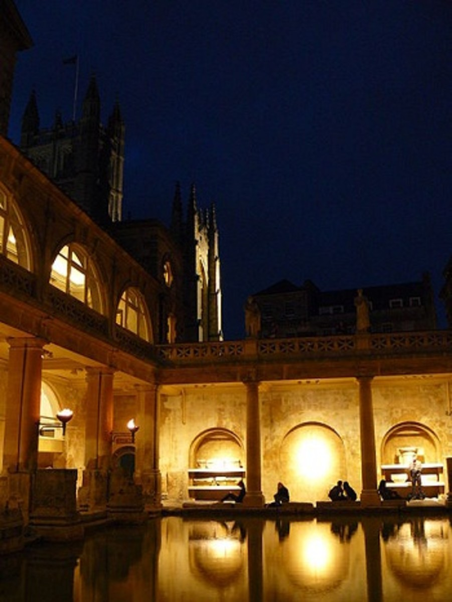 The Roman Baths by torchlight with a glimpse of Bath Abbey in the top left.