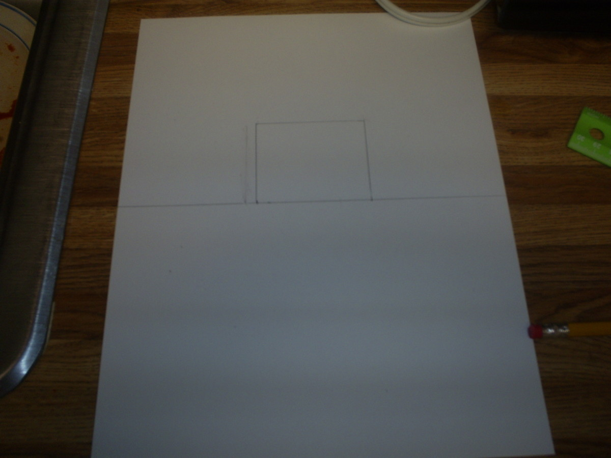 Use the ruler to draw a square centered on the top half of the page.