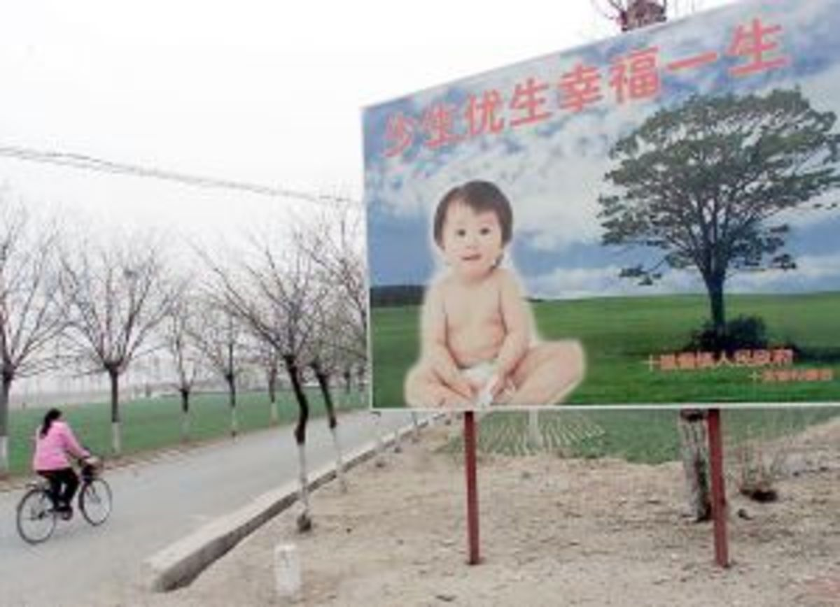 A woman cycles past a billboard encouraging couples to have only one child, along a road leading to a village in the suburbs of Beijing.  China continues to enforce its one child policy to limit its huge population to 1.6 billion by 2050. (Goh Chai H
