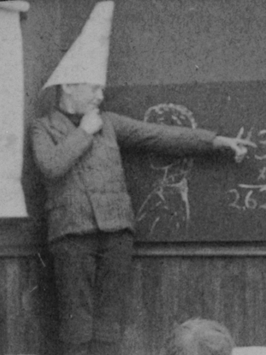 A student in Victorian School wear a dunce cap