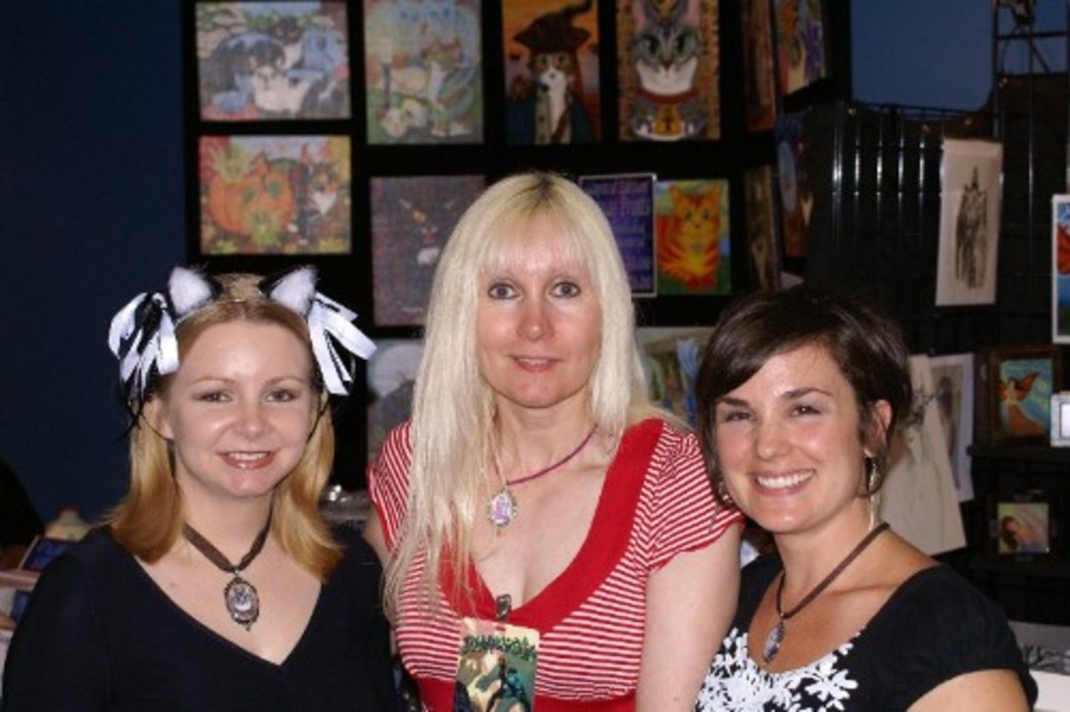 Here I am at Dragon * Con 2008 With artist friends Carrie Hawks on the left, and Deanna Davoil on the right. I'm the tall blonde in the center. Lol! The cat art in the background is the work of talented fantasy cat artist Carrie Hawks.