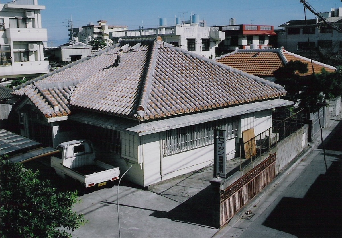 Traditional houses are often found alongside modern apartment buildings. This scene was taken in Isa, Ginowan, Okinawa.