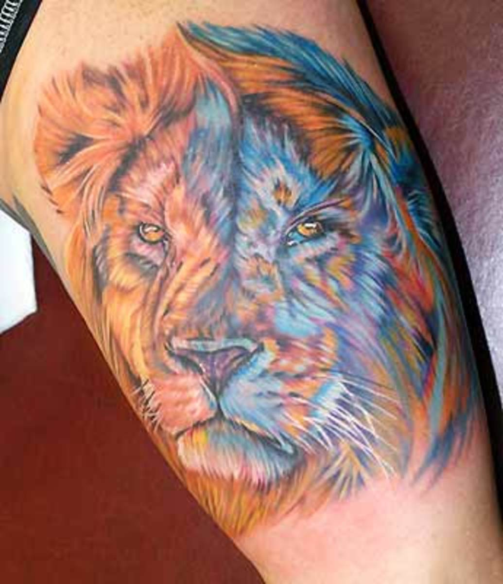 The addition of the blue adds interest to this tattoo.  The artist captured the wildness and magnificence of lions well.