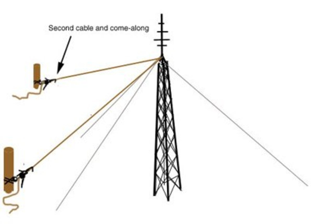 Find a second hard point and attach another cable or rope to the top of the tower and a come-along attached to a tree or post or hardpoint.