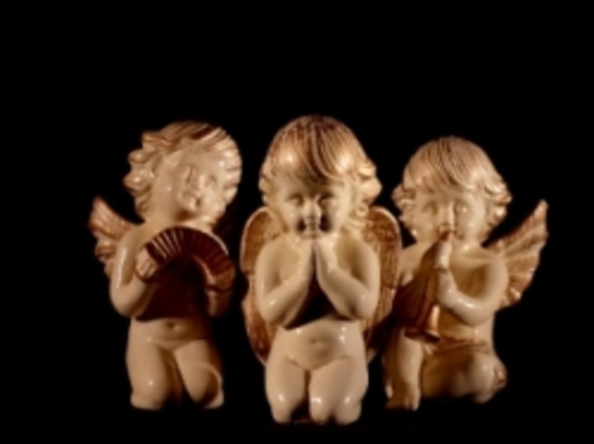 Three ceramic cherubs on their knees