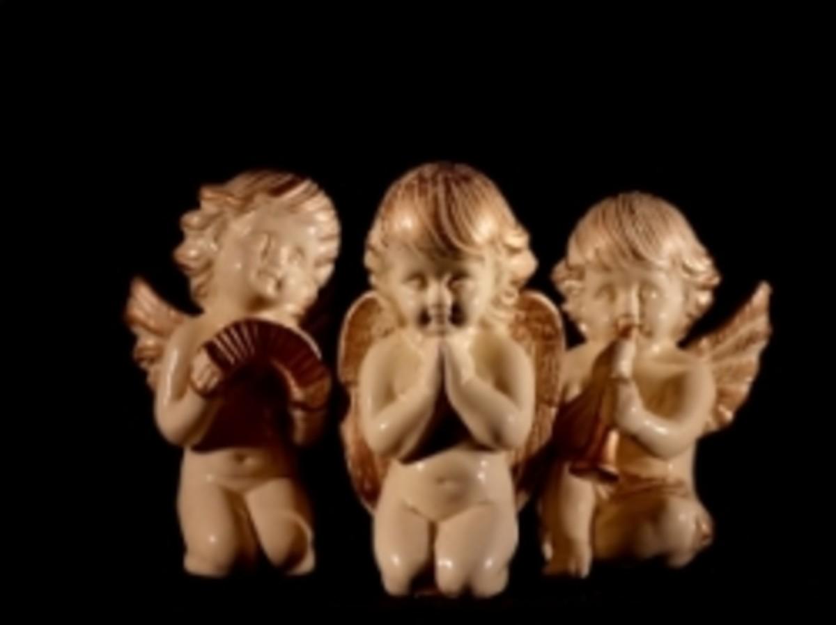 Three ceramic cherubs on their knees