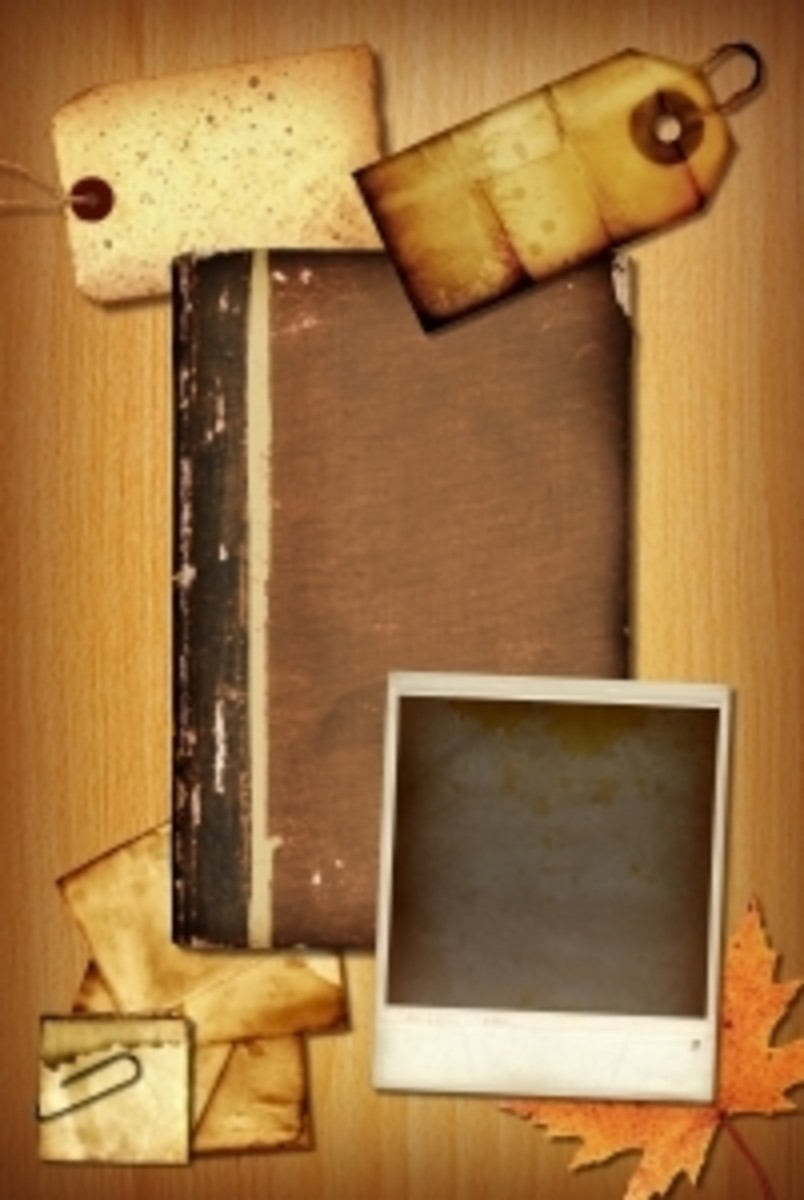 Aged scrapbook materials including a blank book, Polaroid photo, tags, and pieces of paper in sepia tones