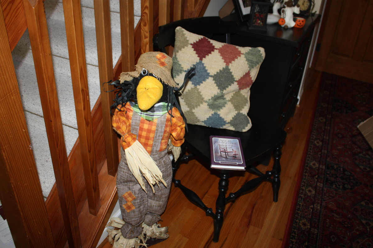 Here an antique chair, rustic pillow and scarecrow look cute together