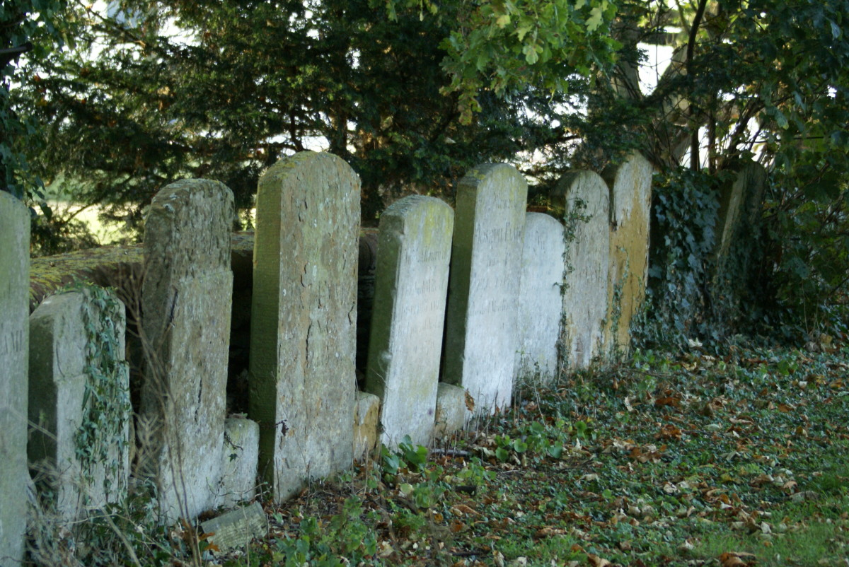 Worn headstones along the western edge of St. Mary's Churchyard in Moulsoe, Buckinghamshire
