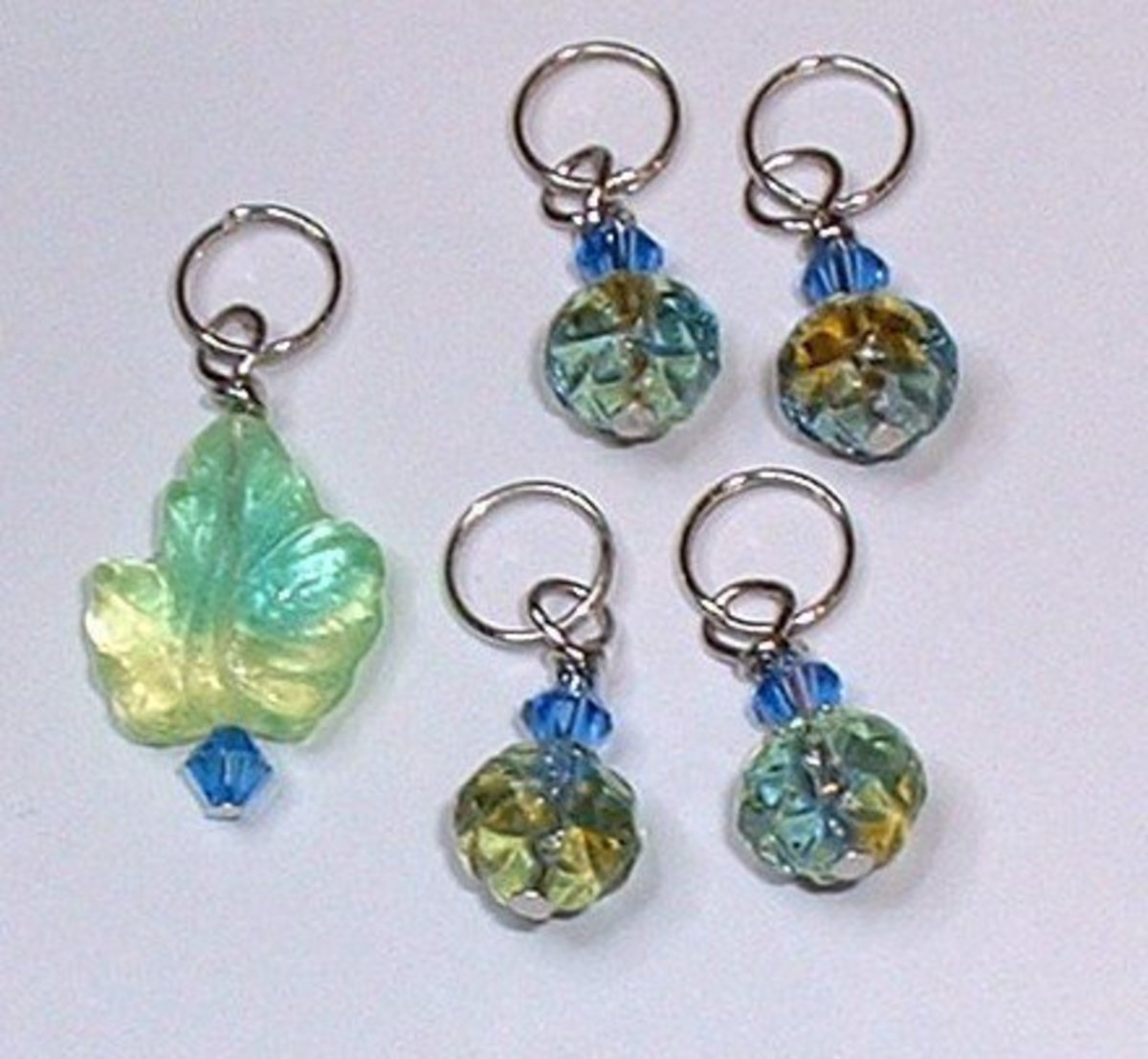 Beaded stitch markers with large glass leaf bead and smaller swirl round beads.
