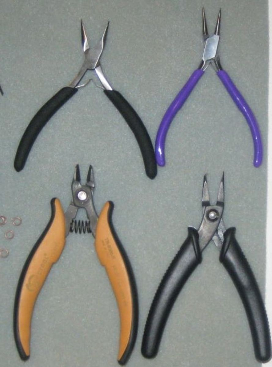 Jewelry tools:  from top left, flat nose pliers (black handle); round nose pliers (purple handle); wire cutter (orange handle); and split ring pliers (black handle).