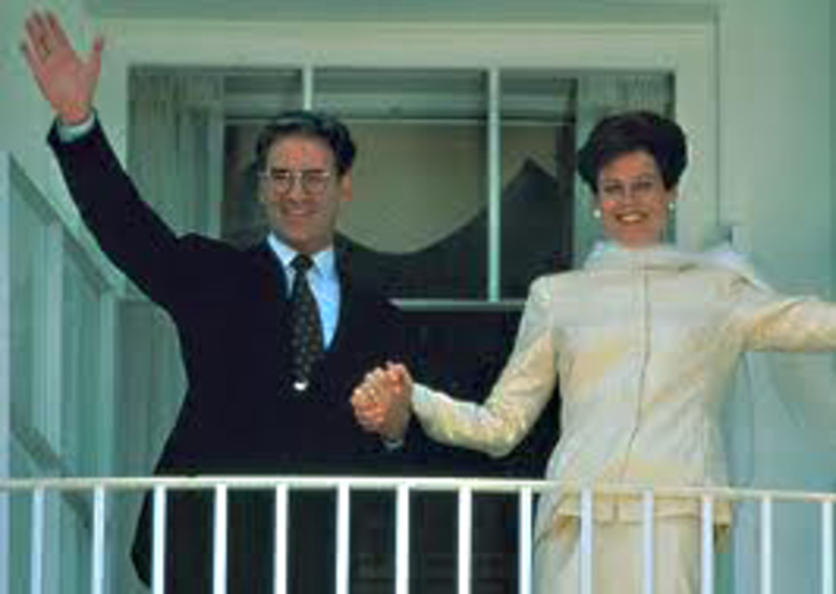 The 'President' and the First Lady (Kevin Kline and Sigourney Weaver) on the White House balcony wave to the crowds on the lawn below