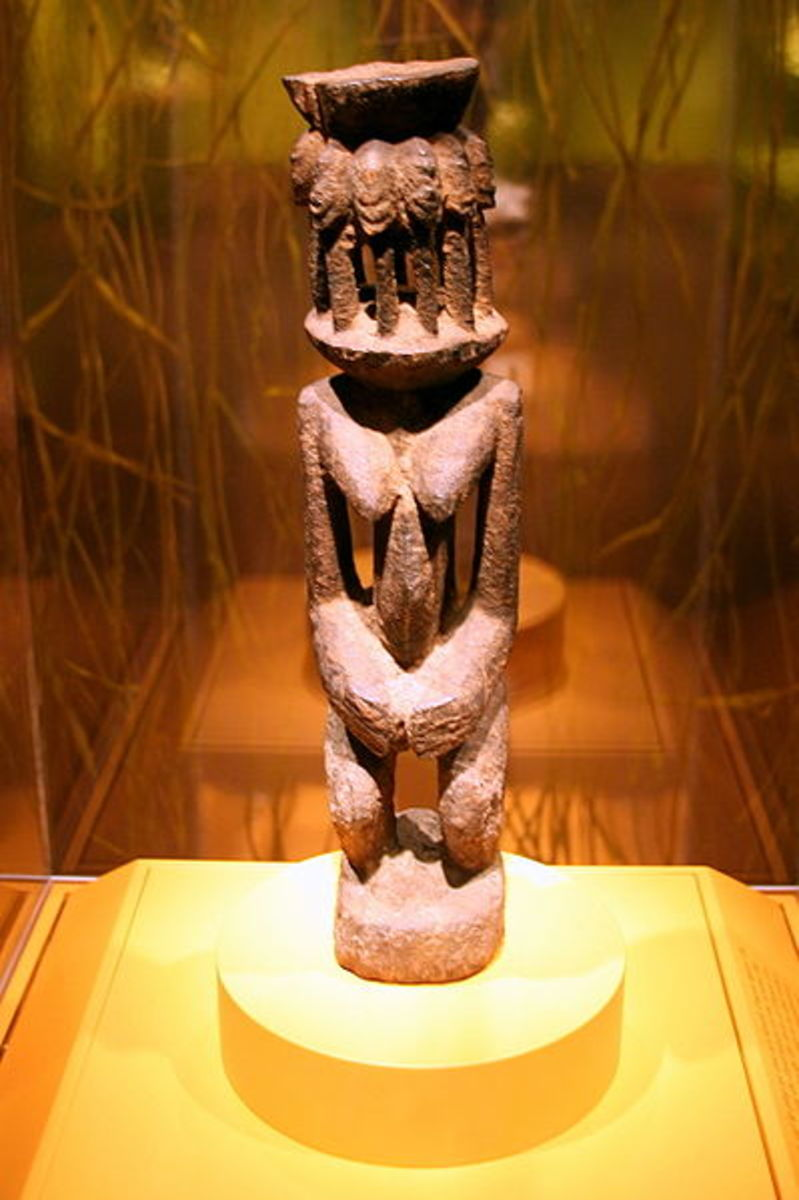 A female Dogon figure who's head is represented by an altar on which are several heads of  the amphibious Nommo