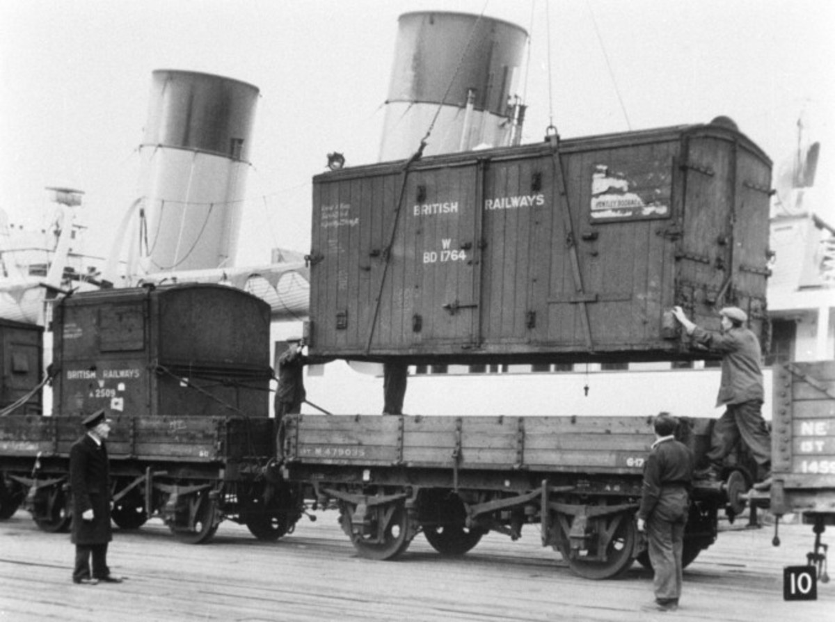 Unloading containers, 1950s - early days yet, no hi-viz here either - not by the book, loading container into 3-plank wagon where there are no chain pockets for securing!