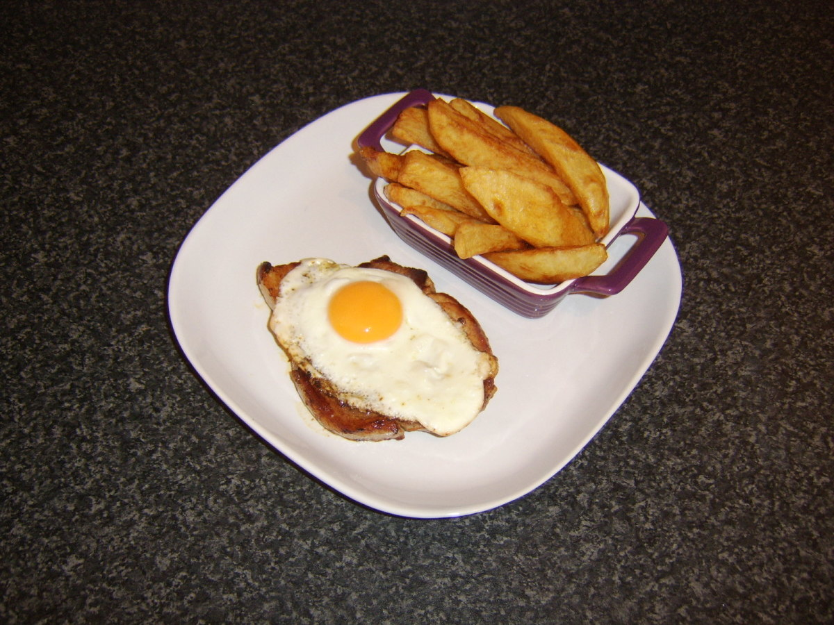 A simply fried pork chop, topped by a fried egg and accompanied by freshly homemade chips makes for an excellent dinner
