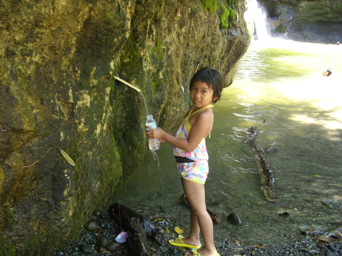 My niece collecting water to drink at Busay Waterfalls.