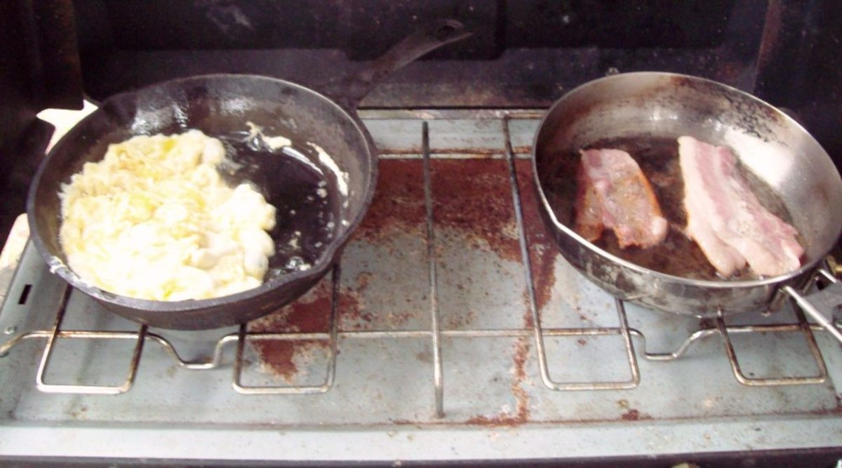 Get the eggs and bacon going at the same time.  They both cook quickly on a propane stove.