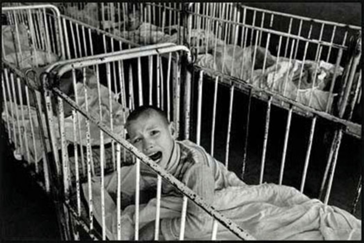 """A Romanian orphan in the early 1990's, surrounded by other orphans. """"Babies who don't get attention when they cry learn to stop crying."""""""