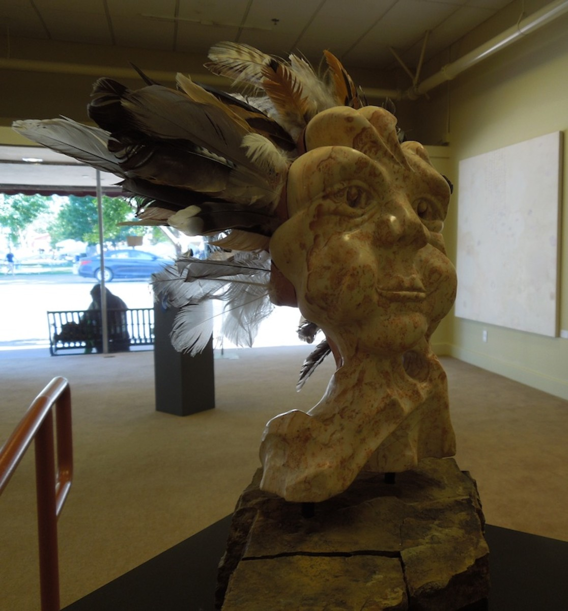 """Iris"" by Catherine Verhulst, made with sandstone, feathers, and clay"