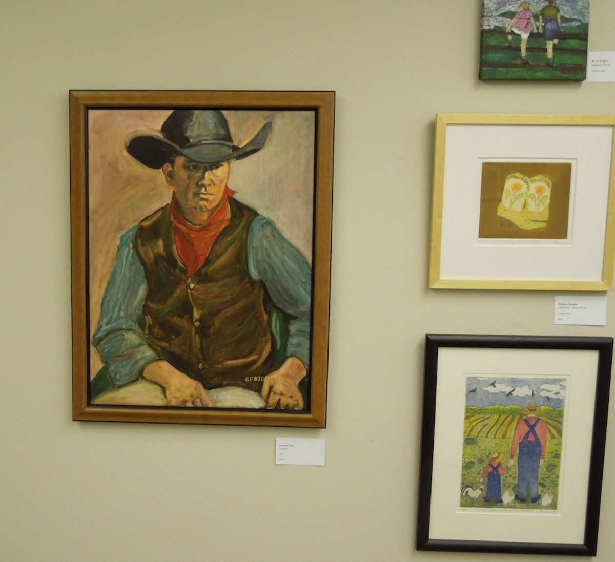 """I call this the western wall. The two paintings above were also on it. To the left is """"Cowboy"""" by Carmen Fojo, in oils. At the lower right is """"Grandfather's Fields"""" by Earlene Vaughn, intaglio print."""